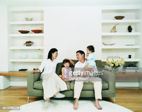 Smiling Family of Four Sitting on a Sofa in a Living Room : Stock Photo