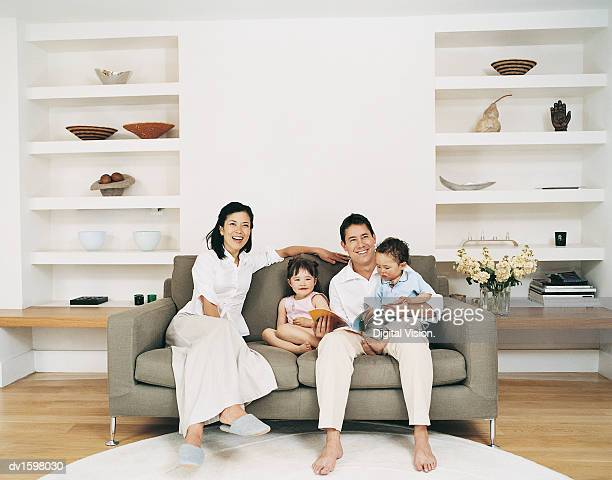 Smiling Family of Four Sitting on a Sofa in a Living Room