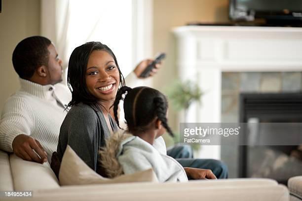 Sonriendo familia en el sofá mientras ve la televisión