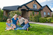 Family of four, including mother, father, and son and daughter sits in front of their beautiful home. They are proud and smiling to be in such a great place.