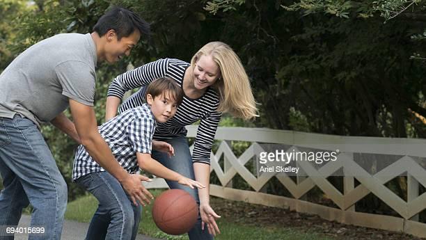 Smiling family playing basketball