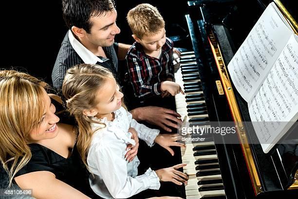 Lächeln Familie zusammen spielen Klavier.