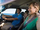 Smiling family riding in minivan