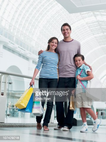 Smiling family shopping together in mall : Stock Photo