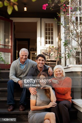 Smiling family sitting on steps outdoors : Stock Photo
