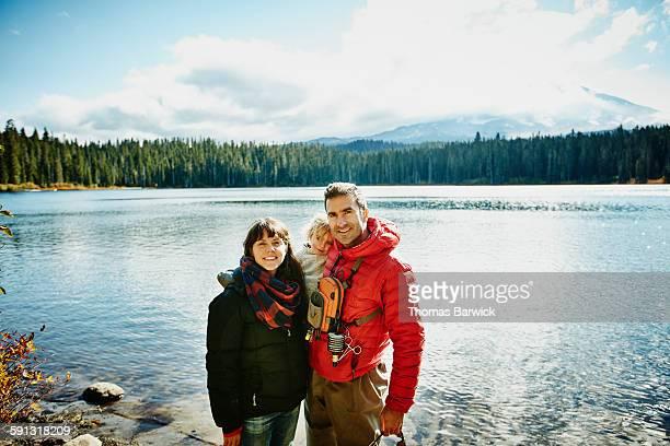 Smiling family standing on shoreline of lake