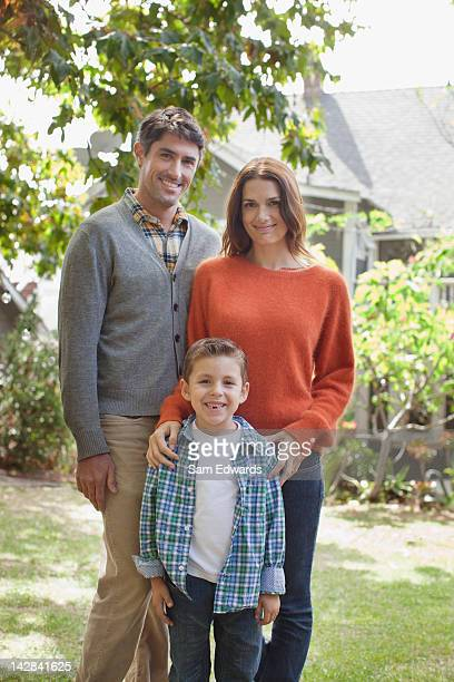 Smiling family standing outdoors together