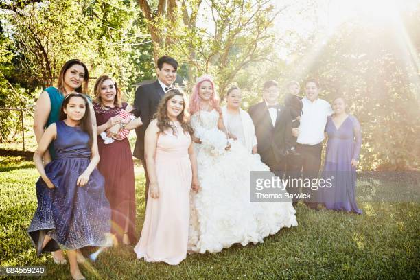 Smiling family surrounding young woman in quinceanera gown in backyard on summer evening