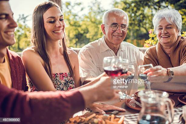 Smiling family toasting with wine in a restaurant.