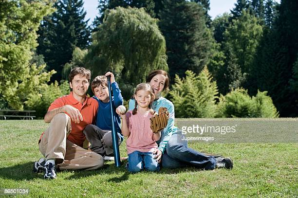 Smiling family with baseball equipment