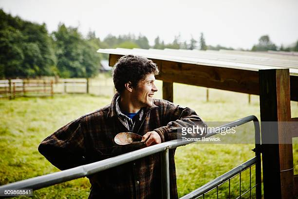 Smiling farmer standing with arm resting on gate