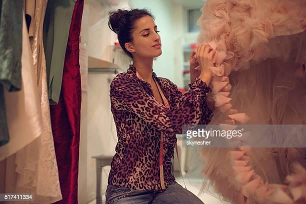 Lächelnd Modedesigner arbeiten mit Kleid in Bekleidungsgeschäft.