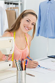 Portrait of a smiling female fashion designer working on her designs in the studio