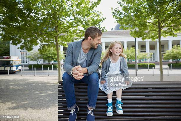 Smiling father and daughter on bench