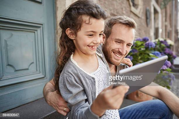 Smiling father and daughter with digital tablet