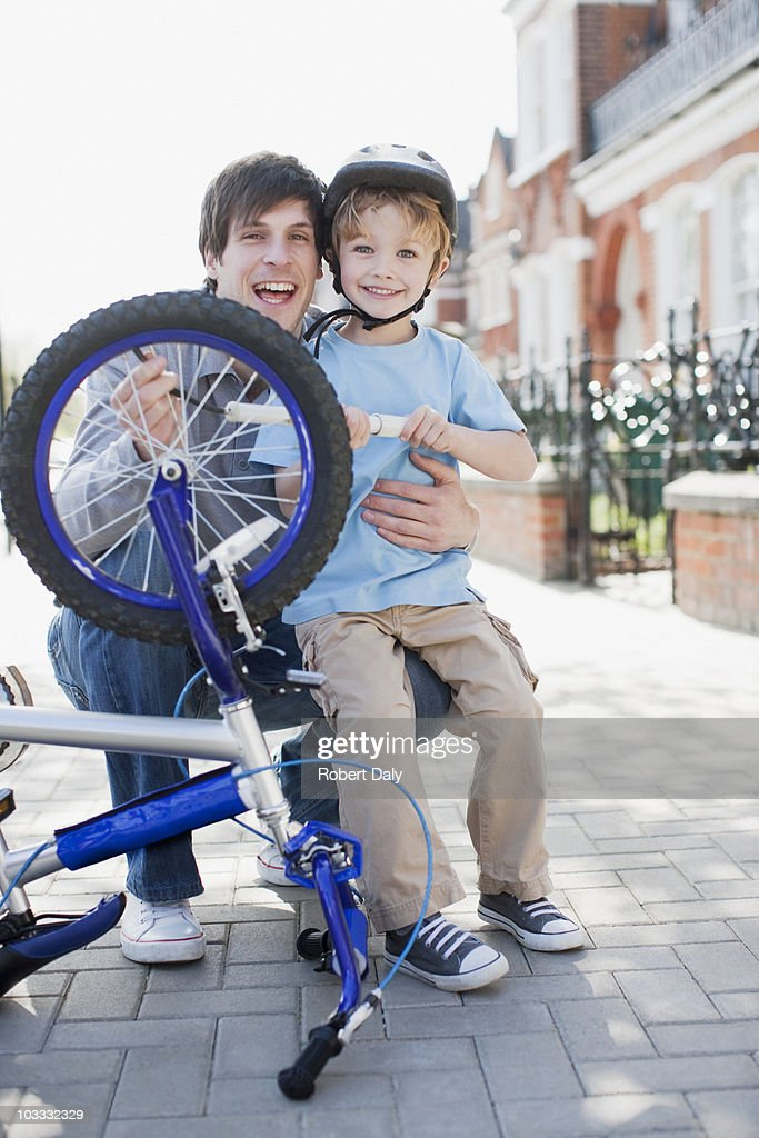 Smiling father and son fixing bicycle tire on sidewalk : Stock Photo