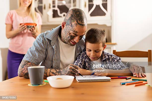 Smiling father and son having fun while coloring together.