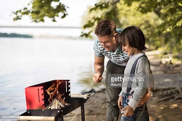 Lächelnd Vater und Sohn Feuer vorbereiten für das barbecue.