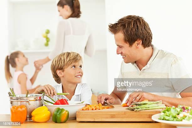 Sorridente pai e filho de Preparar Alimentos