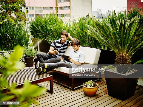 Smiling father and son sitting together on terrace stock for Terrace parent lounge