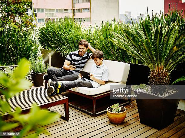 Smiling father and son sitting together on terrace