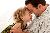 Smiling father and toddler girl touching foreheads