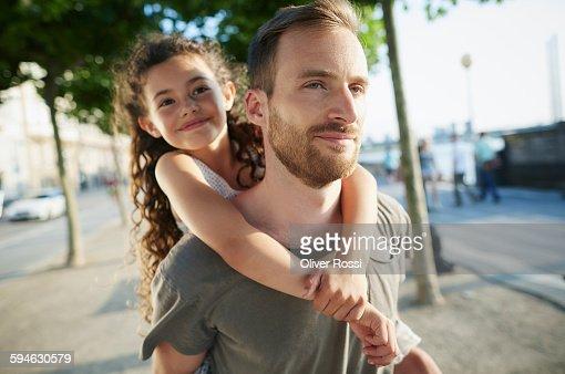 Smiling father carrying daughter piggyback