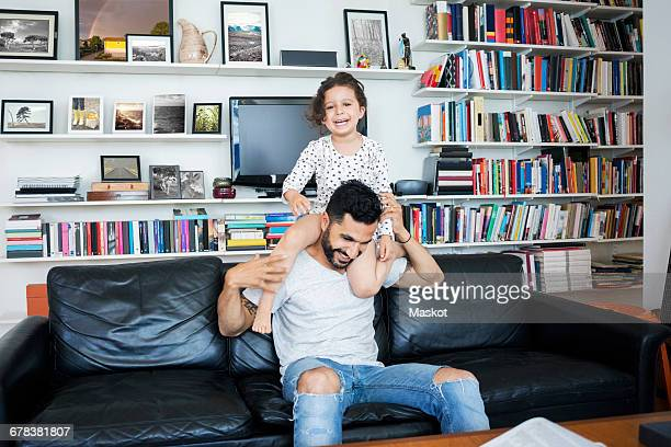 Smiling father carrying daughter while sitting on sofa at home