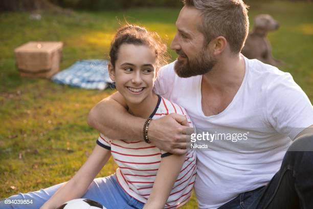 Lächelnden Vater umarmen Tochter auf Wiese im park