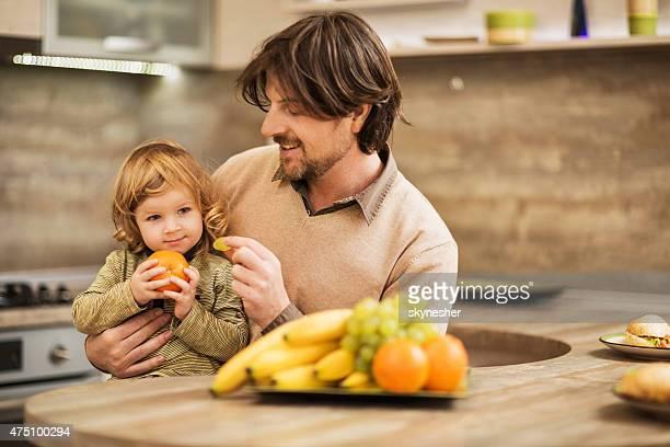 Sorridente Pai amamentar o seu filho com uma Uva.
