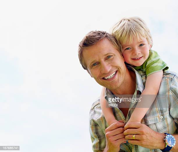 Smiling father giving his son piggyback ride against white