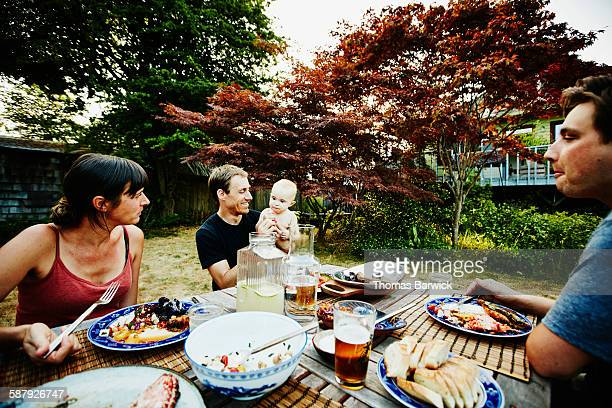 Smiling father holding daughter during barbecue