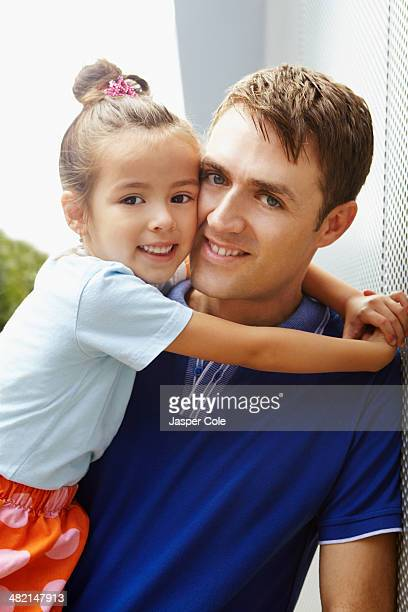 Smiling father holding daughter