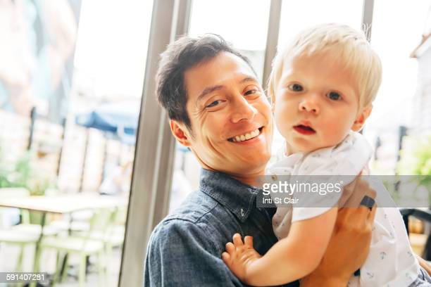 Smiling father holding son by window