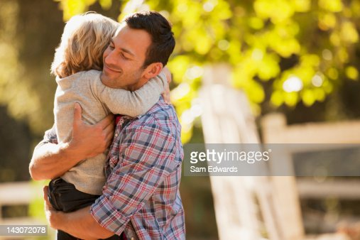 Smiling father hugging son outdoors : Stock Photo