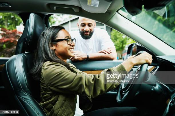 Smiling father leaning in car window giving instructions for daughter learning to drive