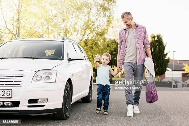 Smiling father looking at son playing with stuffed toy while walking by car on street