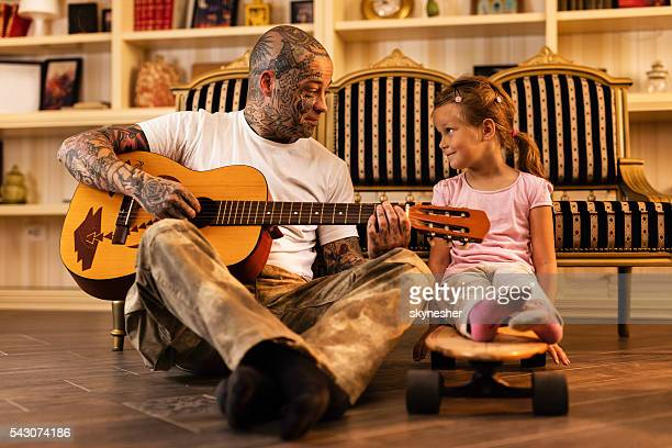 Smiling father playing acoustic guitar and talking to his daughter.