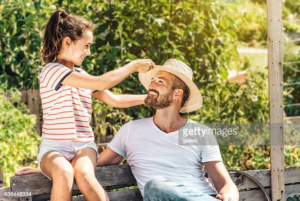 smiling father sitting with teenage daughter in summer garden