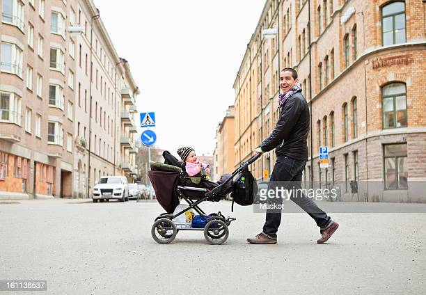 Smiling father walking with cute baby (0-11 months) in stroller