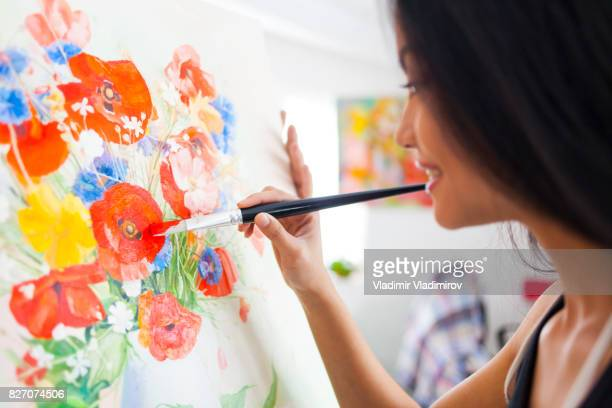 Artiste féminine souriant, au studio de dessin