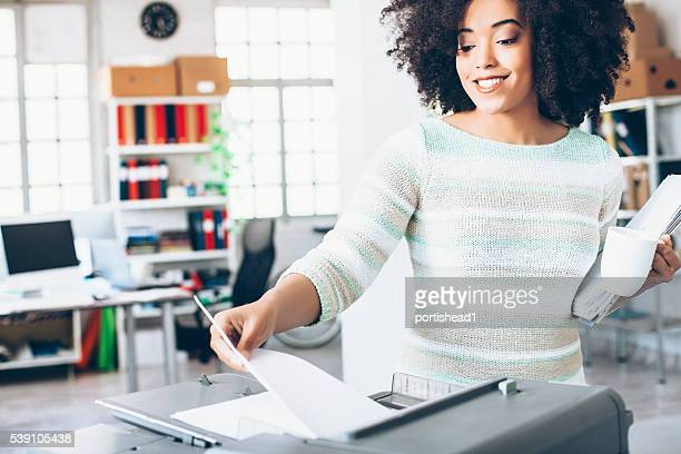 Smiling female assistant using copy machine at work