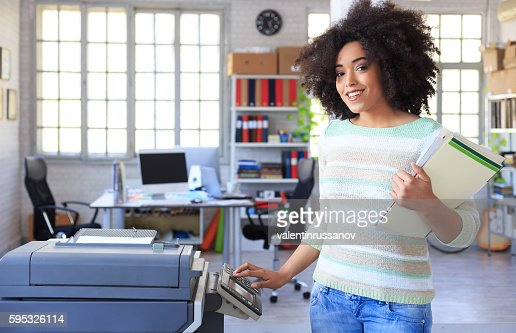 Smiling female assistant using copy machine at workplace