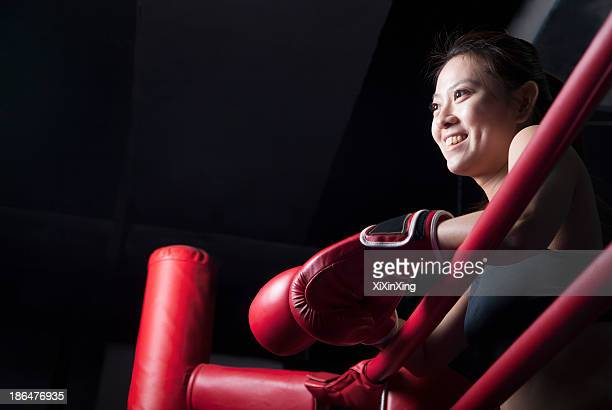 Smiling female boxer resting her elbows on the ring side, looking away, low angle view