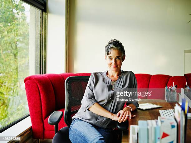 Smiling female business owner sitting at desk