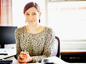 Smiling female businesswoman seated at workstation