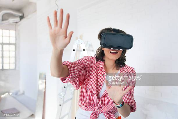 Smiling female construction worker using VR headset