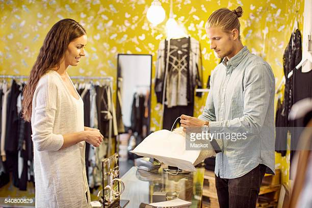 Smiling female customer looking at sales person packing bag at checkout counter in clothing store