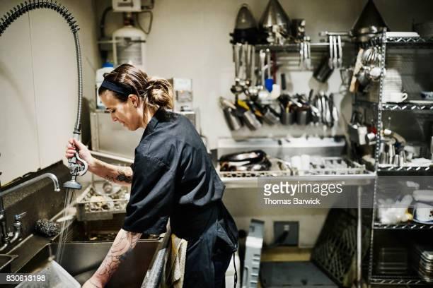 Smiling female dishwasher working at sink in restaurant kitchen