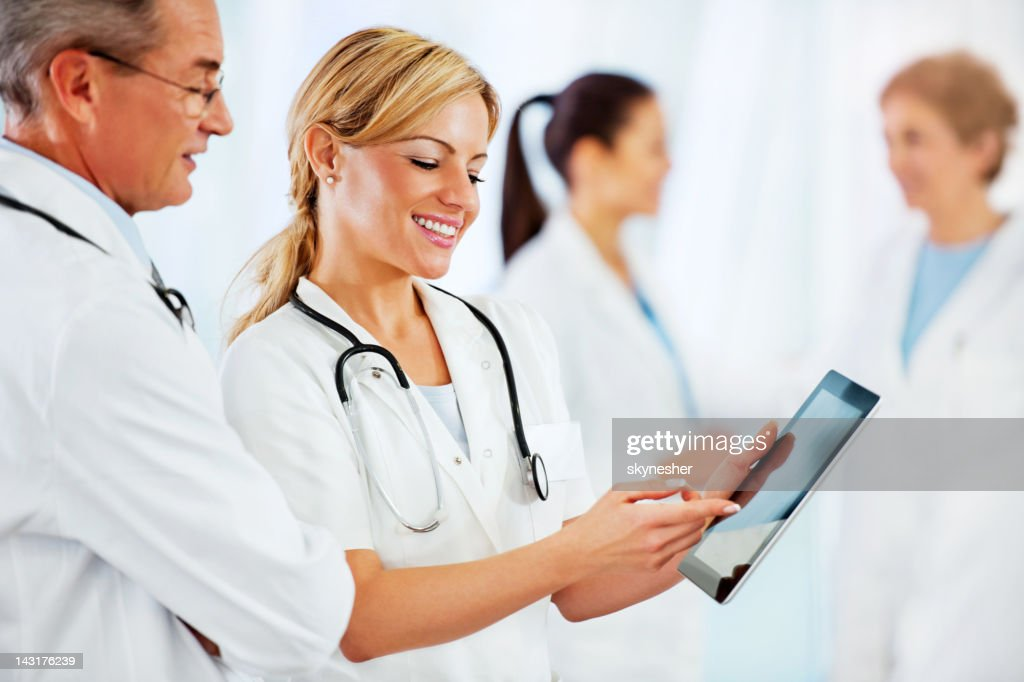 Smiling female doctor showing older colleague medical reports. : Stock Photo